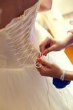 Closeup toned photo of beautiful bride tying up her wedding dress stock photos