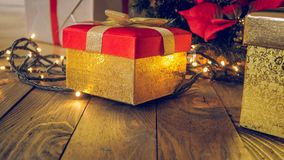 Closeup toned image of golden box with gift on wooden desk against glowing Christmas lights. Closeup toned photo of golden box with gift on wooden desk against stock image