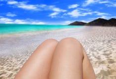 Closeup toned photo of slim female legs tanning on seashore Stock Image