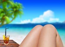 Closeup toned photo of slim female legs tanning on seashore Stock Images