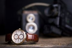 Closeup toned shot of male watches lying on table against photog. Raphy retro set Stock Images
