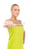 Closeup of toothbrush on foreground with girl smiling on background. Stock Photos