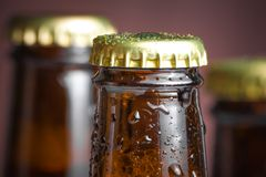Closeup of top of bottle of fresh beer with drops Stock Images