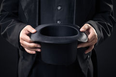 Closeup of top hat in magician hands isolated on dark Stock Photography