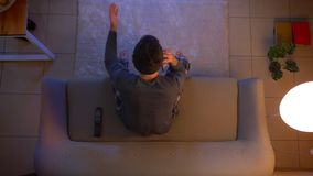 Closeup top shoot of young male watching a football match on TV having a phone call talking with excitement indoors at. Cozy home with lights off in the evening stock video