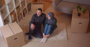 Closeup top shoot of young muslim couple sitting on the floor in a newly bought apartment smiling happily dreaming about stock video