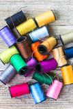 Closeup top view of colorful bobbins with sewing threads piled up on rustic wooden background with copy space royalty free stock images