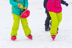 Closeup top view of legs in modern skates on ice rink. Children Friends skating together outdoors at winter frozen lake. Closeup top view of legs in modern stock photo