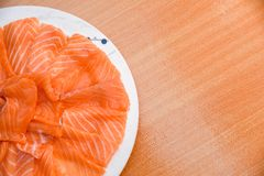 Closeup top view Slided Raw Salmon in white dish on wood blackground royalty free stock photo