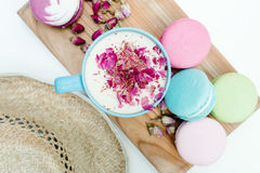 Closeup top view on straw hat and blue cup of aroma cappuccino with french tasty macarons.  Stock Images
