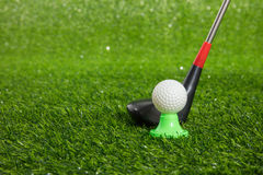 Closeup of toy golf ball and putter. On the green grass Royalty Free Stock Images