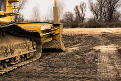 Closeup of tracked excavator at construction area. Dirty yellow excavator on construction site near FK Spartak stadium, local football team in Subotica. Bright royalty free stock image