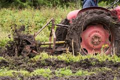 Tractor stuck in mud. Closeup of tractor pulling rotavator (rotary plow) stuck in the mud while trying to bring rough ground under cultivation stock image