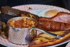 Closeup of traditional tasty scottish english breakfast consisting of beans, sausage, bacon, mushrooms, egg and a black pudding. stock photography