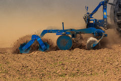Closeup trailer of cultivator raises dust on ploughed field Royalty Free Stock Image