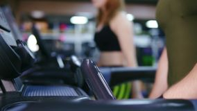 Closeup of a treadmill with an unrecognizable man walking on it in the sport gym warming up before training. Young. Attractive woman is walking behind stock footage