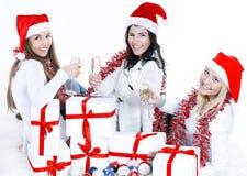 closeup trois jeunes femmes dans des chapeaux de Santa Claus avec Noël Photographie stock libre de droits