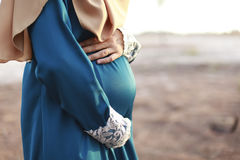 Closeup on tummy of pregnant woman enjoying summer park, wearing Royalty Free Stock Photography