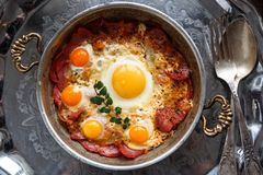 Closeup of Turkish pastirmali and fried egg in a copper pan on wooden table Royalty Free Stock Photography