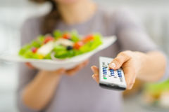 Closeup on tv remote control and salad in hand of woman Stock Photo