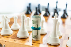 Closeup of twisted money standing on board instead of chess piec Stock Image