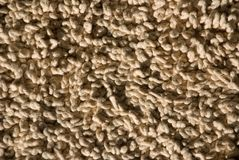 Closeup of twisty wool carpet. Close up of fawn colored woollen rug or mat. twisty wool fiber Royalty Free Stock Photography
