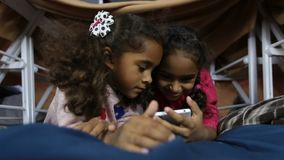 Two smiling kids watching funny pictures on phone. Closeup two adorable mixed race little sisters watching funny pictures on social network via smart phone as stock video footage