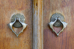 Closeup of two antique copper ornate door knockers over an aged wooden ornate door. Fatih Mosque, Istanbul, Turkey stock photo