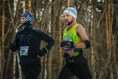 Closeup two athletes middle-aged men running down track in winter forest Royalty Free Stock Photo
