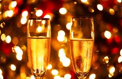 A closeup of two champagne glasses in front of a Christmas tree with blurry lights in the background. royalty free stock images