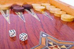 Closeup of two dices on wooden backgammon board. Wooden handmade backgammon board with chips and two dices on white background Stock Image