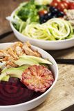 Buddha bowl salads on a wooden table. Closeup of two different buddha bowl salads, made with lettuce, cornsalad, quinoa, zucchini spaghetti, blueberries, beet stock images