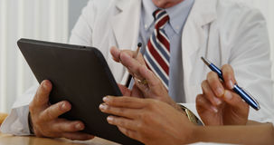 Closeup of two doctors using a tablet in the office Royalty Free Stock Images