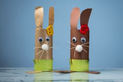 Two Easter bunnies made of toilet paper rolls by a child stock image