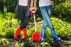Closeup of two girls in gumboots standing at garden at sunny day Royalty Free Stock Photo