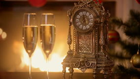 Closeup of two glasses of champagne next to old clock counting minutes to the New Year on table next to burning fireplace. Closeup of two glasses of champagne stock footage