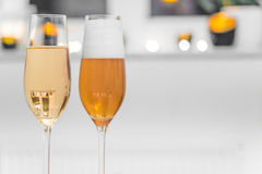Closeup of two glasses filled with champagne and beer Stock Photos