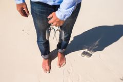 Closeup of two glasses in hand at man walking barefoot on white beach Royalty Free Stock Images