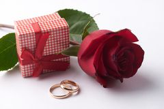 Closeup of Two gold wedding rings with pink gift box and wedding bouquet Royalty Free Stock Images