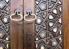 Closeup of two golden ring door knobs over an aged decorated wooden door Stock Images