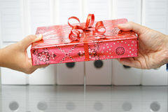 Closeup of two hands exchanging gift in office Stock Image