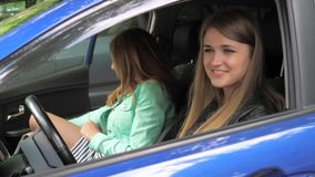 Closeup Of Two Happy Girlfriends Sitting In The Car Saying Goodbye To Each Other. Two cute and cheerful young women say goodbye to each other sitting in the car stock video