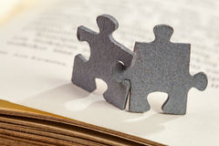 Closeup of two jigsaw puzzle pieces on book Royalty Free Stock Photo