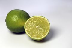 Juicy, Ripe Limes on a White Table. A closeup of two juicy, ripe limes. One lime is cut in half. Photographed on a white table. Photo taken with a macro lens stock photo