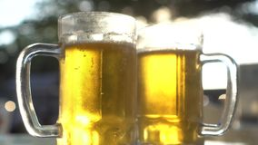 Closeup of two lager beer mugs with sun rays. Closeup of two fresh lager beer mugs with sun rays in hot summer day stock video