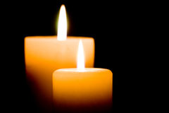 Closeup of two lit candles on black background. Stock Images