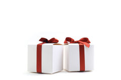 Closeup of two little gift boxes with red ribbons Royalty Free Stock Images