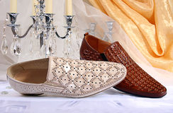 Closeup of two male shoes and candlestick. On the background of draped fabric Stock Photography