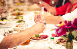 Closeup of two men clinking glasses with vodka at restaurant Stock Images