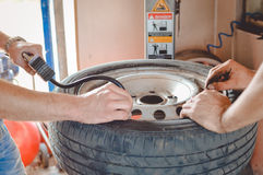 Closeup of two men pumping up old wheel in garage Stock Images